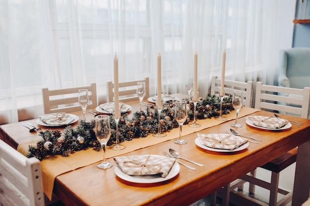 Uitzicht over moderne keuken met witte kasten en bruine tafel gedecoreerd met natuurlijke groene dennentakken en kerstkrans. kerst versiering.