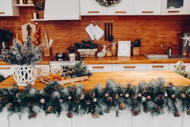 Uitzicht over mooie witte keuken met kerstversiering over kasten en keukenplank. op de kast staat een kerstkrans. natuurlijke dennenboomtakken met dennenappels.