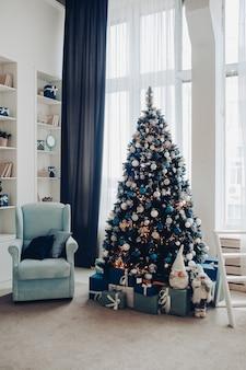 Uitzicht over witte moderne kamer ingericht voor kerstvakantie. versierde en verlichte kerstboom, open haard met dennentak, kaarsen en handgeschept papier sterren in open haard.
