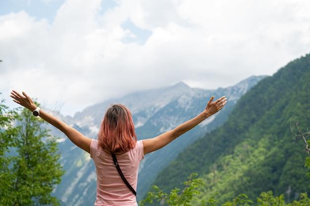 Uitzicht van achteren op een jonge vrouw die buiten in de groene natuur staat en naar bergen kijkt met haar armen wijd gespreid.