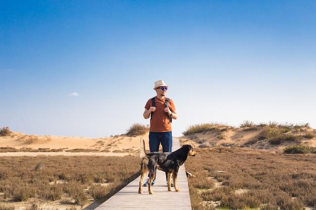 Uitzicht van achteren op een man die met zijn hond loopt op een weg die door een prachtig landschap leidt.