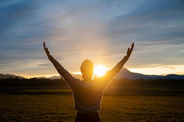 Uitzicht van achteren op een vrouw die het leven omarmt en buiten in een prachtige weide staat met haar armen hoog geheven terwijl de ondergaande zon fel gloeit tussen haar hoofd en arm.