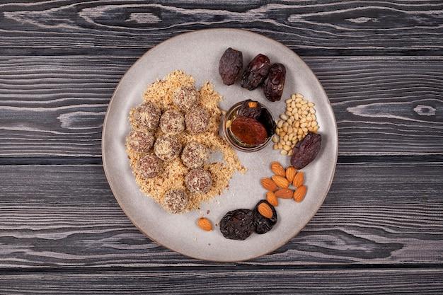 Uitzicht van boven. bord met energieballen en ingrediënten op een donkere houten tafel. rustieke stijl.