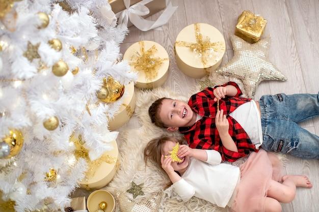 Uitzicht van boven broer en zus dolgelukkig met kerstmis