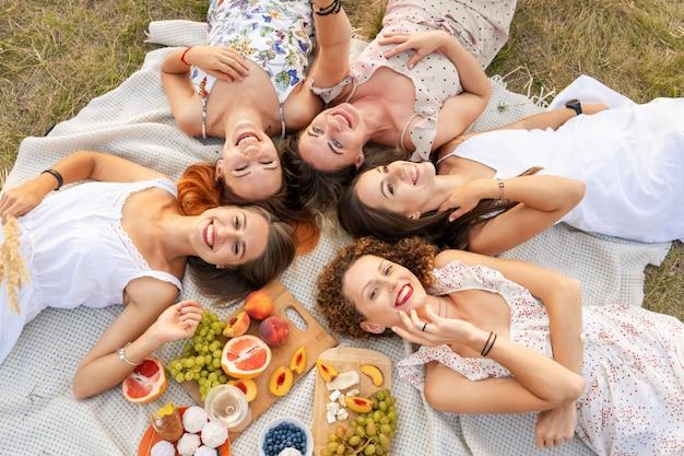 Uitzicht van boven. gezelschap van mooie vriendinnen hebben plezier en genieten van een picknick buiten.