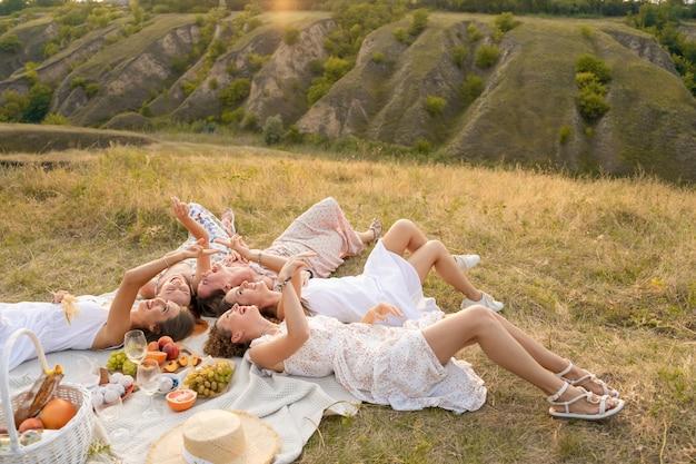 Uitzicht van boven. het gezelschap van mooie vriendinnen hebben plezier en genieten buiten van een picknick