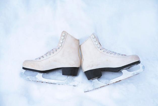 Uitzicht van boven. oude, vintage witte kunstschaatsen op witte sneeuw