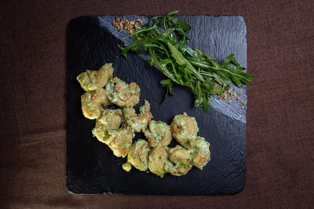 Uitzicht van bovenaf garnalen in wasabisaus en rucola op een zwart bord