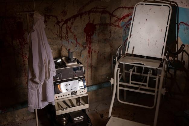 Uitzicht van bovenaf op elektrisch schokkend apparaat in de buurt van medische jurk die aan de hanger hangt en enge stoel met bloedbevlekte muur voor concept over marteling of eng halloween-thema