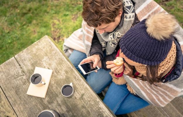 Uitzicht van bovenaf op jonge mooie paar onder deken op zoek naar smartphone en muffin eten in een koude dag met zee en donkere bewolkte lucht op de achtergrond