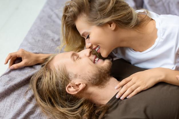 Uitzicht van bovenaf verliefde paar in bed ze knuffelen en kussen