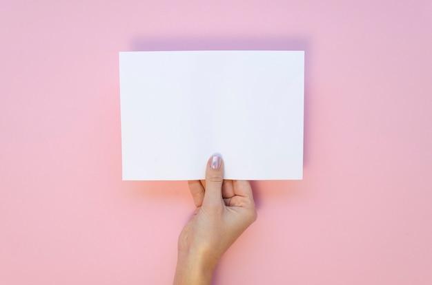 Uitzicht van bovenaf vrouwelijke hand houdt blanco vel papier mockup op een pastel roze achtergrond.