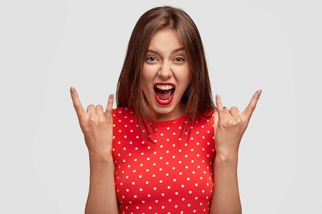 Uitzicht van coole europese vrouw maakt rock gebaar, roept met waanzin