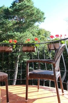 Uitzicht van kamer naar balkon met hortensia's in bloempot en rotan stoel