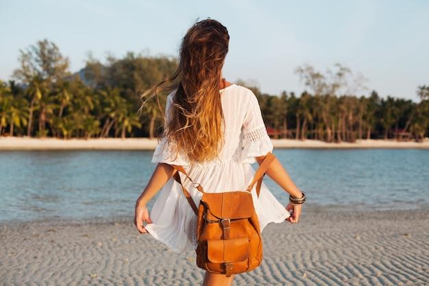 Uitzicht vanaf achterkant mooie vrouw in witte jurk zorgeloos lopen op tropisch strand met lederen rugzak.