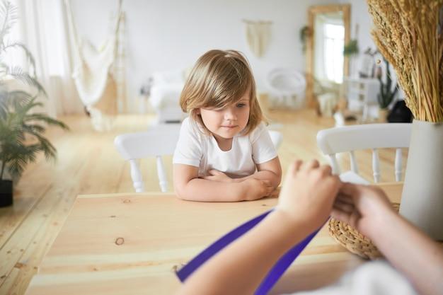 Uitzicht vanaf achterkant van onherkenbaar kind handen met violet vel papier. binnen schot van schattig klein meisje in wit t-shirt zit aan bureau kijken naar haar oudere broer origami maken. selectieve aandacht