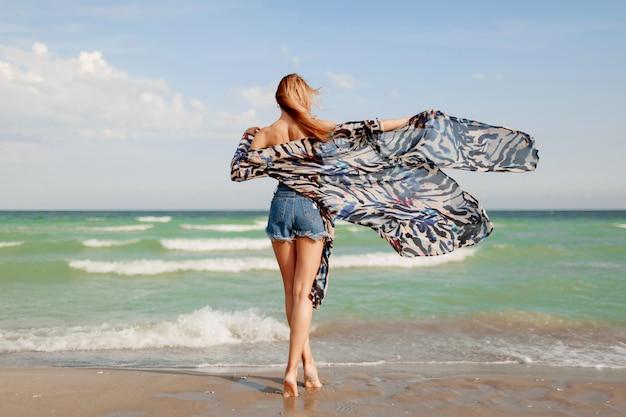 Uitzicht vanaf achterkant van slim tan roodharige meisje in stijlvolle tropische outfit poseren op geweldig strand in de buurt van de oceaan.