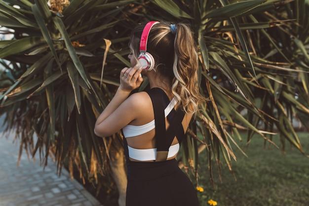 Uitzicht vanaf achterkant vrolijke geweldige vrouw in sportkleding, met lang krullend haar, luisteren naar muziek via koptelefoon in tropische stad. zonnige ochtend, palmbomen, ware emoties, gezonde levensstijl, training.