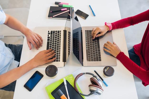 Uitzicht vanaf avove op handen van jonge man en vrouw die op laptop in co-working office werken