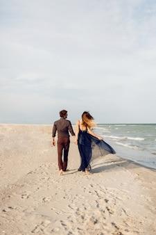 Uitzicht vanaf de achterkant. elegante verliefde paar wandelen langs het strand. romantische momenten. wit zand en oceaangolven. tropische vakantie. volledige hoogte.
