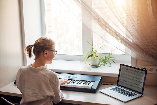 Uitzicht vanaf de achterkant jonge vrouw speelt een synthesizer, het lezen van notities op een laptopscherm. zelfstandig thuis piano leren spelen. passie voor muziek, hobby's, vrije tijd, zelfontplooiing.