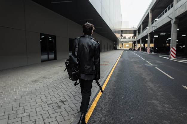 Uitzicht vanaf de achterkant op een modieuze jonge man met trendy kapsel in oversized leren zwarte jas in jeans in coole laarzen met een rugzak op straat in de stad. stijlvolle man in casual jeugdkleding