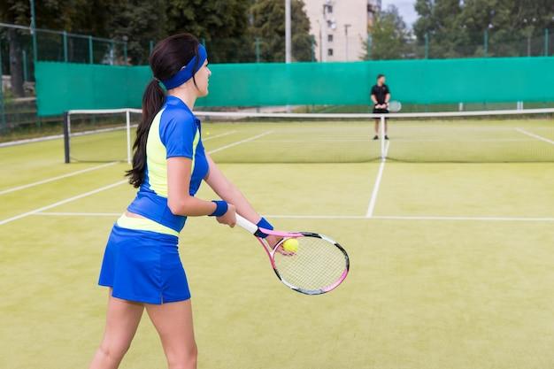 Uitzicht vanaf de achterkant op een tennisspeelster die een sportkleding draagt die tennissen op een rechtbank buiten in de zomer