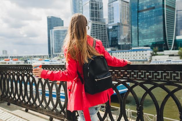 Uitzicht vanaf de achterkant op jonge hipster vrouw in roze jas, jeans lopen in straat met rugzak en koffie luisteren naar muziek op koptelefoon, zonnebril dragen