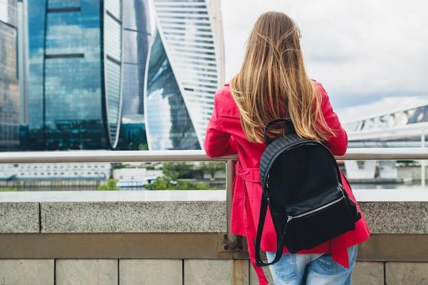 Uitzicht vanaf de achterkant op jonge hipster vrouw in roze jas lopen op trappen in straat met rugzak en koffie luisteren naar muziek op koptelefoon, zonnebril dragen