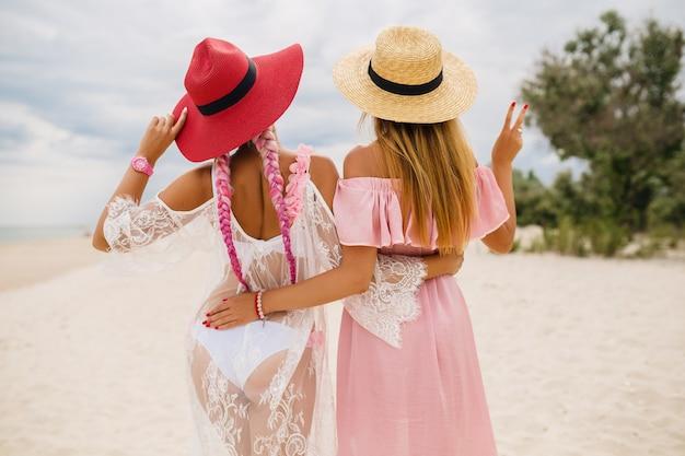 Uitzicht vanaf de achterkant op twee mooie stijlvolle vrouw op strand op vakantie, zomerstijl, modetrend, strooien hoeden dragen, modetrend, roze en kanten jurk, sexy outfit
