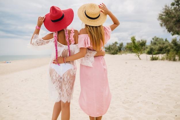 Uitzicht vanaf de achterkant op twee mooie stijlvolle vrouw op strand op vakantie, zomerstijl, modetrend, strooien hoeden, modetrend, roze en kanten jurk, sexy outfit dragen