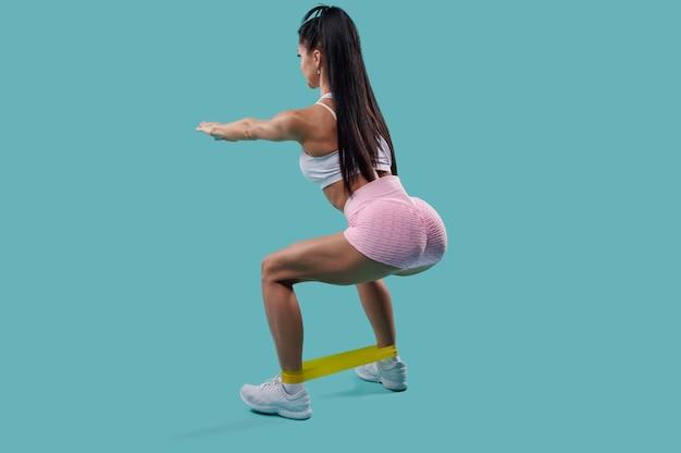 Uitzicht vanaf de achterkant van de jonge sportieve vrouw in witte top en roze sportbroek doet hurken met elastische fitnessband geïsoleerd