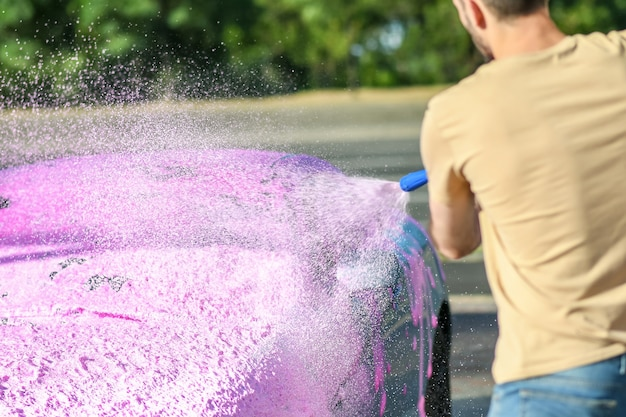 Uitzicht vanaf de achterkant van de man die de auto wast