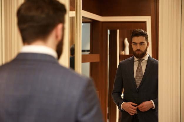 Uitzicht vanaf de achterkant van de mens in de spiegel kijken