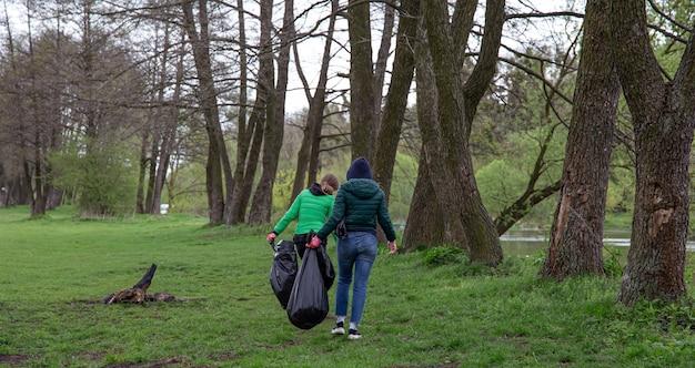 Uitzicht vanaf de achterkant van een meisje dat het afval opruimt bij de uitgang naar het bos, in de lente