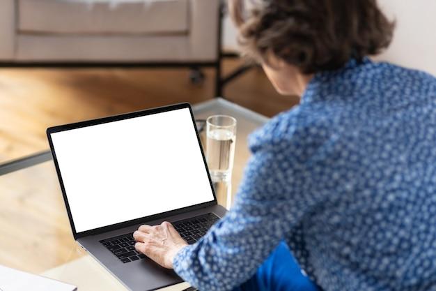Uitzicht vanaf de achterkant van een oude zakenvrouw die werkt tijdens het gebruik van een laptopcomputer met een leeg scherm