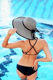 Uitzicht vanaf de achterkant van een vrouw in een bikini en een modieuze hoed die in het zwembad staat