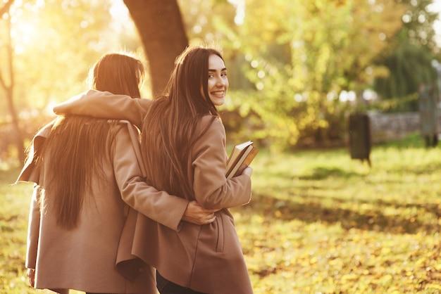 Uitzicht vanaf de achterkant van jonge lachende brunette tweeling meisjes knuffelen en plezier in casual vacht wandelen in herfst zonnig park op onscherpe achtergrond. een van hen kijkt achteruit en houdt boeken vast.