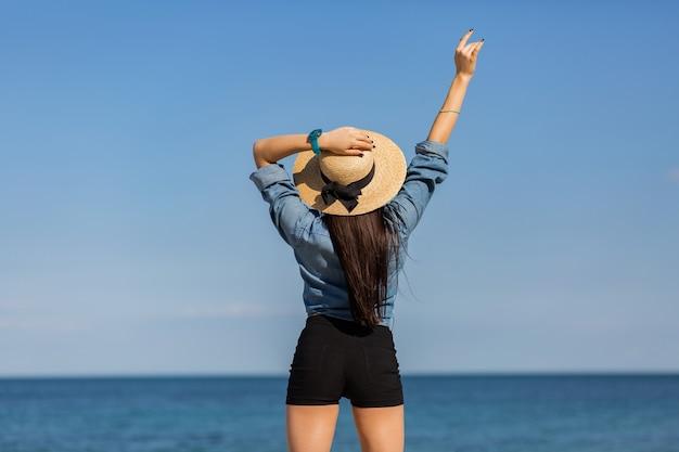Uitzicht vanaf de achterkant. vrouw in strooien hoed, met figuur kijkend op de zee.
