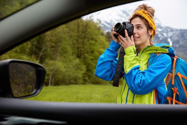 Uitzicht vanaf de auto van professionele jonge vrouw fotograaf neemt foto's op camera, wandelingen op groen veld met berglandschap