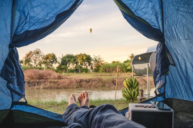 Uitzicht vanaf de binnenkant van de tent met ontspannen en vissen in het moeras