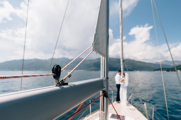 Uitzicht vanaf de boeg van een zeiljacht jonggehuwden staan op de achtersteven van een zeilboot tegen de achtergrond
