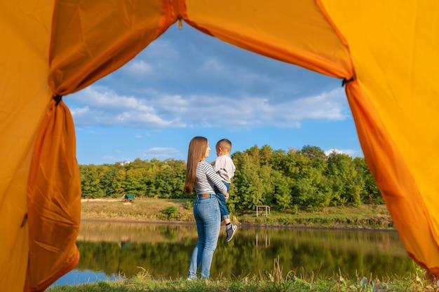 Uitzicht vanaf de camping tent. het meisje geniet van het kind van de aardholding in haar handen. wandelen met kind