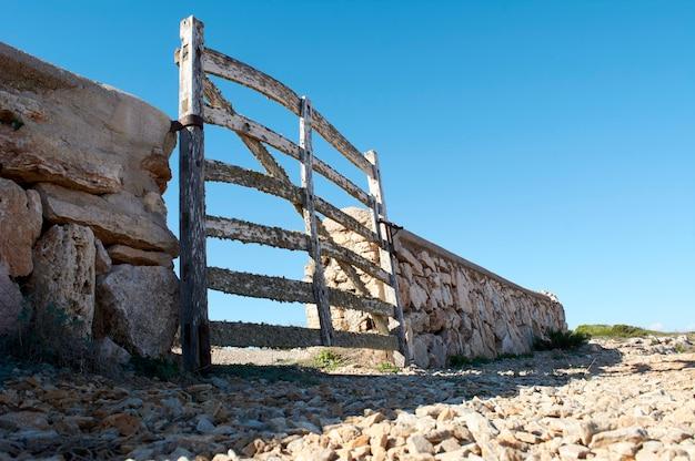 Uitzicht vanaf de grond, van typische houten deur, met korstmossen, in stenen muur naast de weg