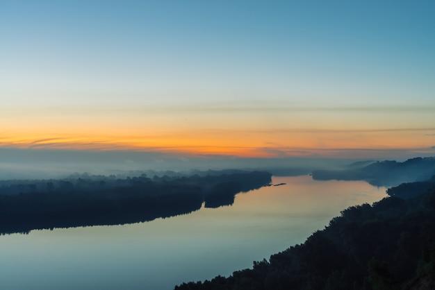 Uitzicht vanaf de hoge oever op de rivier. riverbank met bos onder dikke mist.