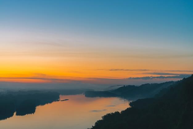Uitzicht vanaf de hoge oever op de rivier. rivieroever met bos onder dikke mist. gouden dageraad weerspiegeld in water. gele gloed in schilderachtige predawnhemel. kleurrijk ochtend atmosferisch landschap van majestueuze aard.