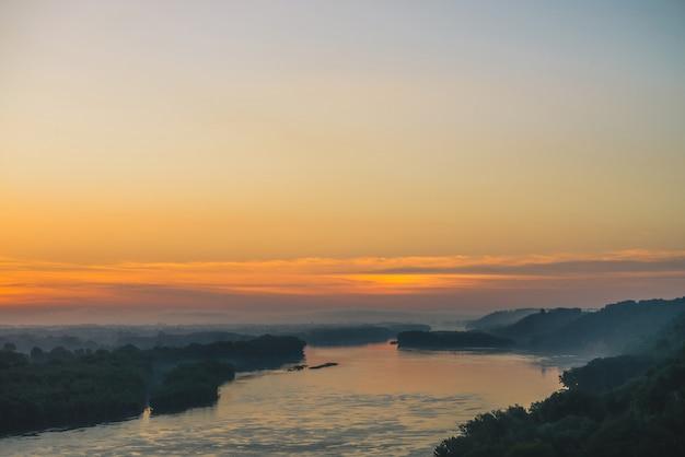 Uitzicht vanaf de hoge oever op de rivier. rivieroever met bos onder dikke mist.