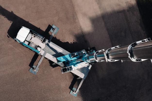 Uitzicht vanaf de hoogte van de hoogste autokraan, die open is op de parkeerplaats bij het glazen gebouw in de stad en klaar om te werken.