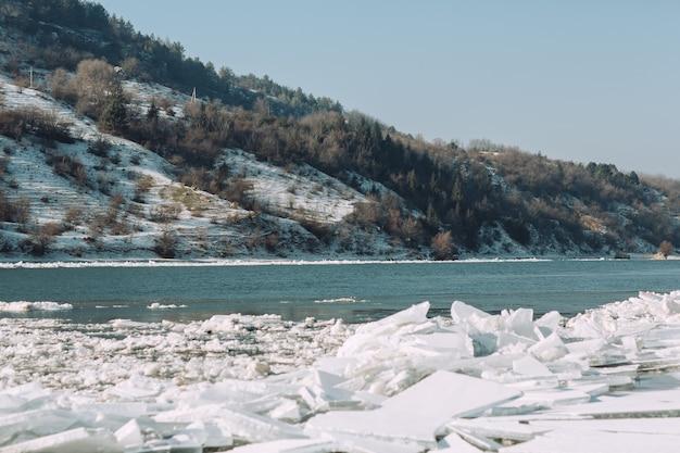 Uitzicht vanaf de oever van de rivier op de ijsschotsen, de besneeuwde heuvels en het blauwe water in zonnige dag