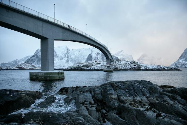 Uitzicht vanaf de onderkant van de brug en fotografen in het vissersdorp iconische hamnoy in lofoten, noorwegen met rode huizen rorbu.